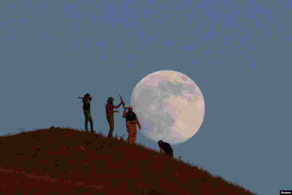 Luftëtarët e Ushtrisë Çlirimtare Siriane qëndrojnë në majë të një kodre, me hënën në sfond, në jug të qytetit Nawa, në Daraa Governorate.