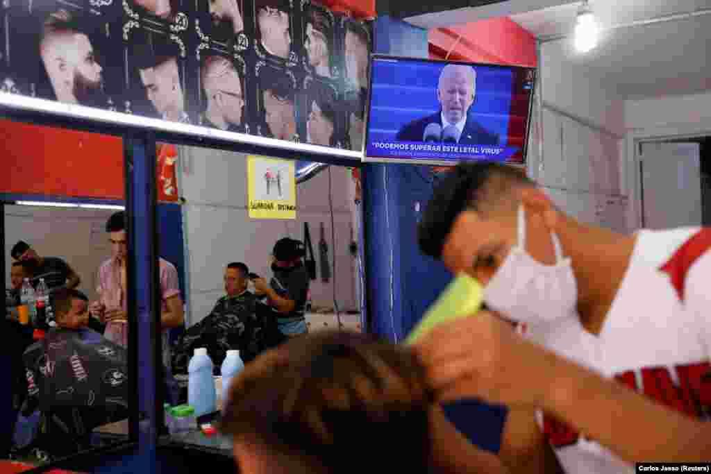 Гондурастык мигрант чач тарачта отуруп Байдендин ант берүү аземин көрүп жаткан учуру. Мексика.