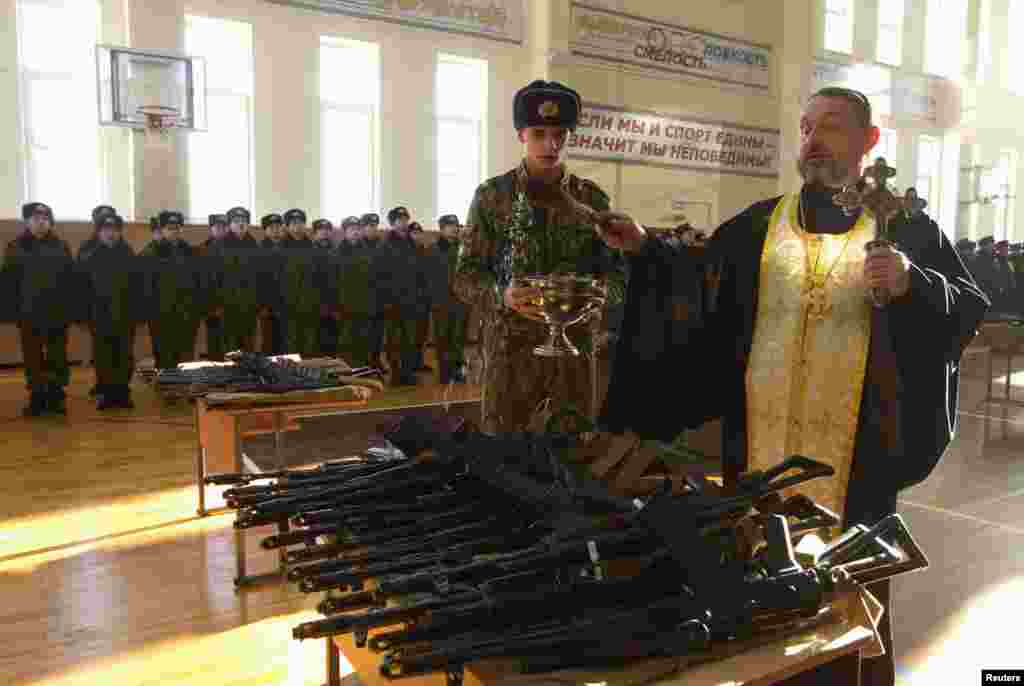 An Orthodox priest blesses rifles during a ceremony where new recruits receive their weapons at a military base of the Belarusian Interior Ministry in Minsk. (Reuters/Vasily Fedosenko)
