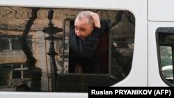 Полиция көлігі ішінде жасақ қызметкерімен арпалысып, терезеден басын шығармақ болған наразы. Алматы, 22 сәуір 2021 жыл.