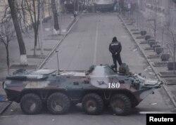 Милиционер стоит на боевой машине, заблокировавшей подход к правительственным зданиям. Киев, 20 февраля 2014 года.