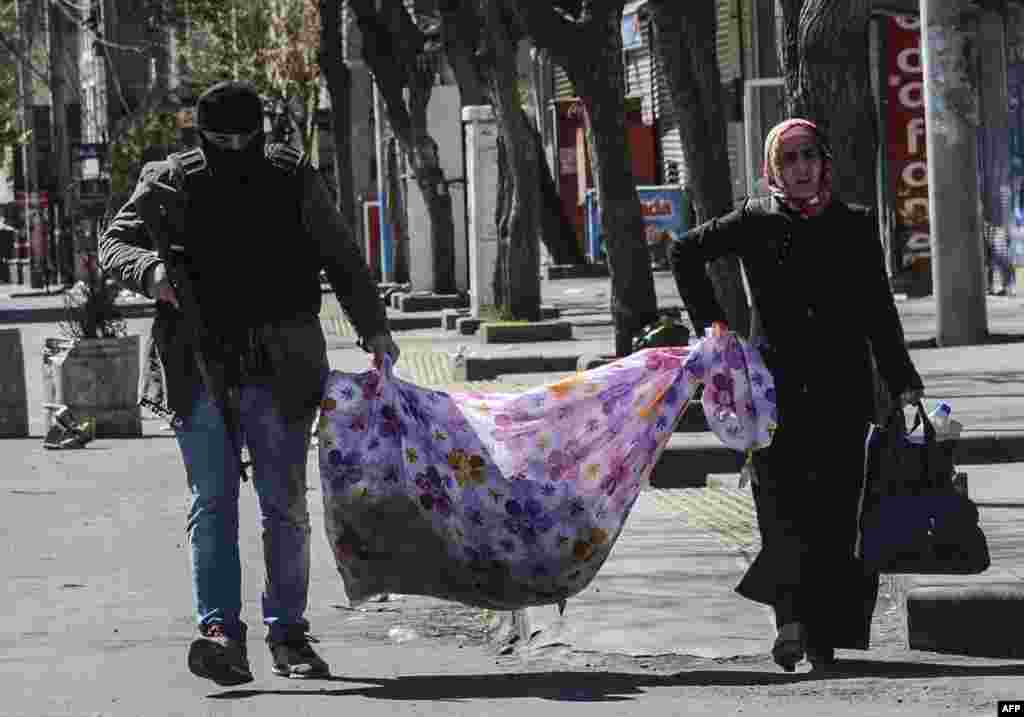 An armed Turkish police officer helps a woman carry her belongings as she leaves her house during clashes in central Diyarbakir on March 17. (AFP/Ilyas Akengin)