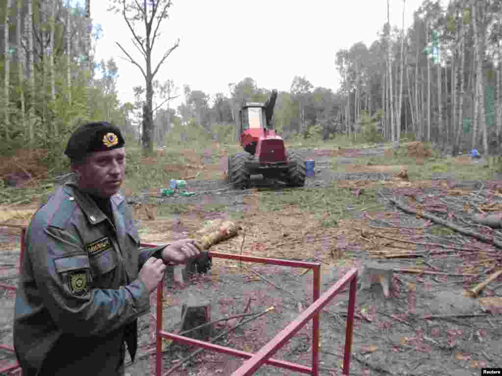 A policeman guards the site of the planned highway in late August.