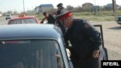 Рейд кезінде көлікті тоқтатып, тексеріп жатқан полиция қызметкерлері. (Көрнекі сурет.)