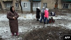 Женщина смотрит на воронку, образовавшуюся после обстрелов Макеевки. Донецкая область, 27 января 2015 года.