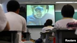 Студенты в Пекине на трансляции лекции китайских астронавтов с борта космической станции Tiangong-1. 20 июня 2013 года.