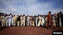 Internally displaced Pakistani men line-up to be registered at the UNHCR-supported Jalozai camp.
