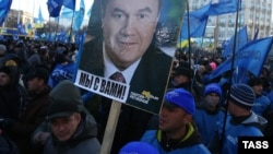"""We are with you"" says the sign under the photograph of Ukrainian President Viktor Yanukovych at a pro-government rally in Kyiv on December 14."