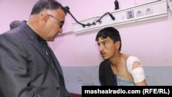 Khost Governor Mohammad Halim Fidai talks with an one of those injured on March 3.