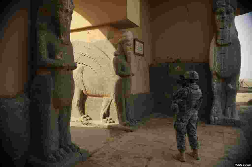 A member of the U.S. Air Force documents sculptures on the entrance to an ancient palace in November 2008.