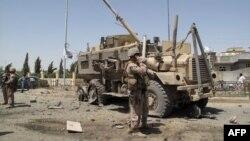 Një ushtar amerikan qëndron në vendin ku ka ndodhur një sulm vetvrasës me veturë-bombë në Lashkar Gah,Afganistan, 28 gusht 2013