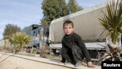 Дамаск маңындағы Муадхамия ауданында гуманитарлық көмекті тосып отырған бала. Сирия, 17 ақпан 2016 жыл.