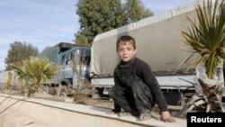یک کودک سوری در نزدیکی کامیونهای حامل مواد غذایی در مناطق تحت محاصره اطراف دمشق نشسته است.