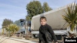 Сирийский мальчик возле колонны грузовиков с гуманитарной помощью