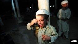 Pakistan. Karaçi. Polis əməliyyatı zamanı mədrəsədən çıxan uşaq ağlayarkən