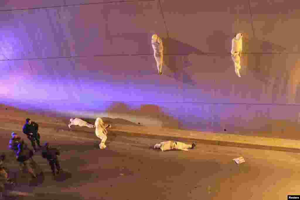 """La Vanguardia / El Guardian өчен эшләүче Мексика фотографы Кристофер Ванегасның бу фотосы """"Ялгыз фотода замана мәсьәләләре"""" номинациясендә өченче урын алды. Фотода Мексиканың Салтилло шәһәрендә күпергә асып куелган ике кеше мәете һәм җирдә ятучы тагын өч кеше мәете янына килгән полиция хезмәткәрләре сурәтләнә."""