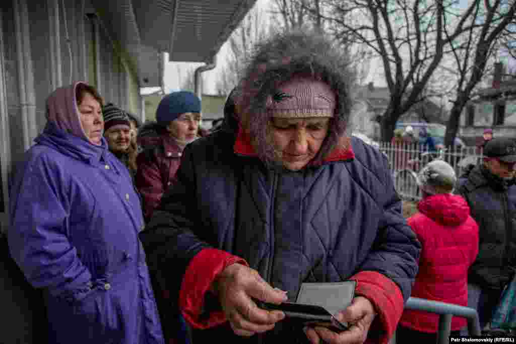 Svetlana Ivanovna, a widow, gets her documents ready at a humanitarian aid distribution center.