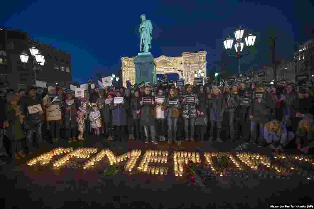 "People stand in front of the word ""Kemerovo,"" made up of candles, to commemorate the victims of the March 25 fire in a shopping mall in the Siberian city of Kemerovo, in Moscow's Pushkin Square, on March 27. (AP/Aleksandr Zemlianichenko)"