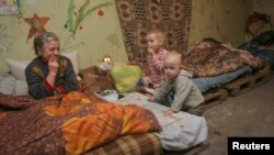 Residents sit in a basement used as a bomb shelter in Donetsk on December 30.