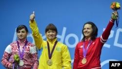 Қазақстандық ауыр атлет Майя Манеза (ортада) олимпиада тұғырында алтын алып тұр. Лондон, 31 шілде 2012 жыл.