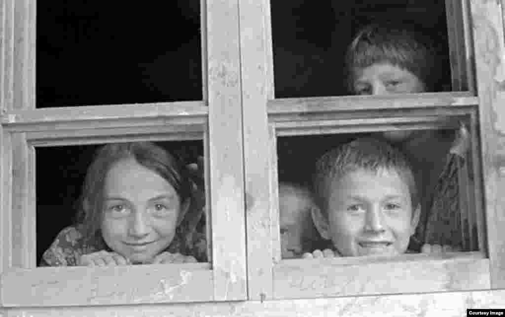 Любознательные дети выглядывают в окно.
