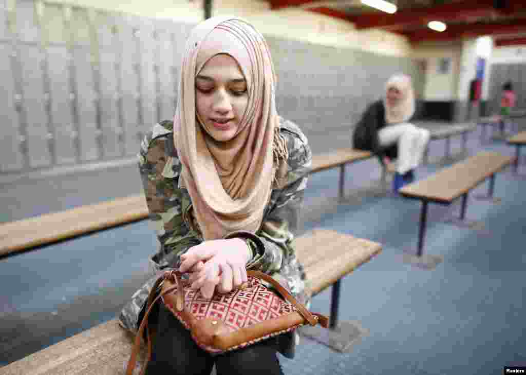 "Ameera, 12, waits to go ice skating in east London. Ameera first wore the hijab as part of her primary school uniform. She started to wear it full time at age 9 because most of her friends did. Her mother told her: ""You don't have to wear it. You're still young!"" Ameera says she loves to wear the hijab and has as many as 60 or 70 different scarves."