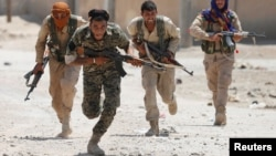 Syrian Kurdish fighters from the People's Protection Units (YPG) run across a street in Raqqa on July 3.