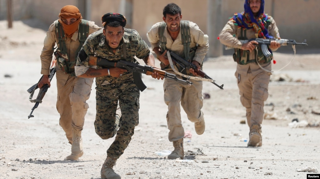 Kurdish fighters from the People's Protection Units (YPG) run across a street in Raqqa on July 3.