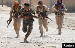 Бойцы курдского отряда ведут бой на улице в городе Ракка. 3 июля 2017 года.