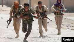 Kurdish fighters from the People's Protection Units (YPG) battle in Raqqa in July