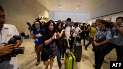 Жінка (у центрі кадру), родичі якої перебували на борту зниклого літака, в аеропорту в Сінгапурі