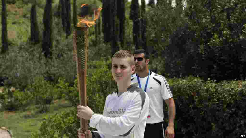 British boxer Alexandros Lucas holds the torch with the Olympic flame during the torch relay after the lighting ceremony in ancient Olympia on May 10, 2012.
