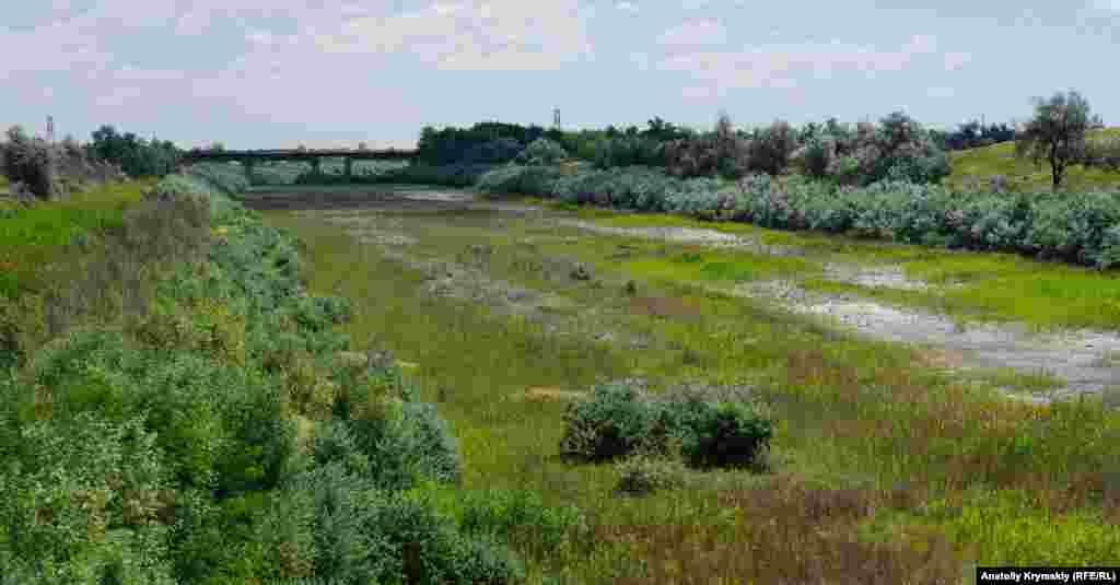 На дні висохлого Північно-Кримського каналу залишилися купи сміття. І він заріс густою рослинністю. Вдалині видніється залізничний міст через канал