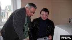 Сябры АГП Юры Істомін і Мікалай Уласевіч абмяркоўваюць праграмы кандыдатаў удэпутаты.