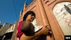 Молодая уйгурка несет на руках уснувшего ребенка. Урумчи, 10 июля 2009 года.