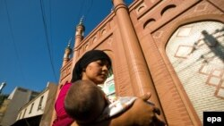 FILE: A young ethnic Uyghur woman carrying a baby walks in front of a mosque in Urumqi.