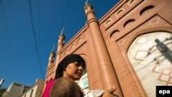 Молодая уйгурка с ребенком на руках перед мечетью в Урумчи, Синьцзян-Уйгурский автономный район, Китай, l2009. Архивно-иллюстративное фото