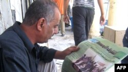 An Iraqi shoeshiner reads the paper in Baghdad.
