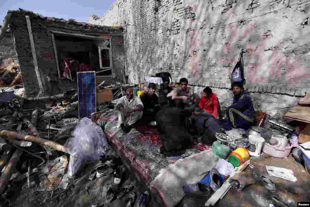 Residents have lunch inside their damaged house after a suicide car-bomb attack on a government security building in Kabul on April 19. (Reuters/Mohammad Ismail)