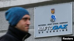 A man walks past the headquarters of the Ukrainian energy company Naftogaz in central Kyiv.
