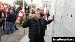 Участники акции начали стучать камнями по металлическим панелям. «Чтобы достучатся до Тамар Жвания», – заявил Звиад Куправа (справа)