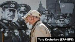 Мужчина в защитной маске идет перед огромным граффити, посвященным победе во Второй мировой войне. Москва, май 2020 года.