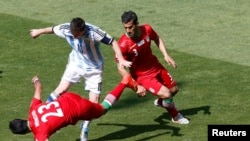 Argentina's Lionel Messi fights for the ball against Iran's Mehrdad Pouladi (L) and Ehsan Hajsafi (R) during their 2014 World Cup Group F soccer match. June 21, 2014