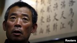 Китаец на фоне стенда на китайском языке. Иллюстративное фото.