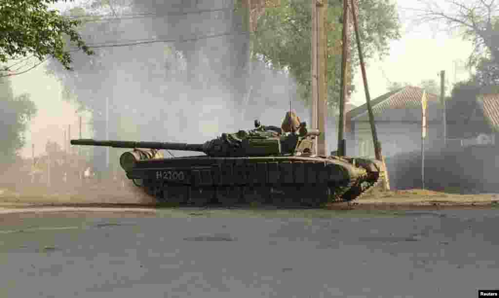 Танк проезжает по улице российского города Матвеев Курган вблизи российско-украинской границы в Ростовской области. Конвой из 9 танков был доставлен в область поездом днем ранее - 25 мая, сообщает корреспондент Рейтер