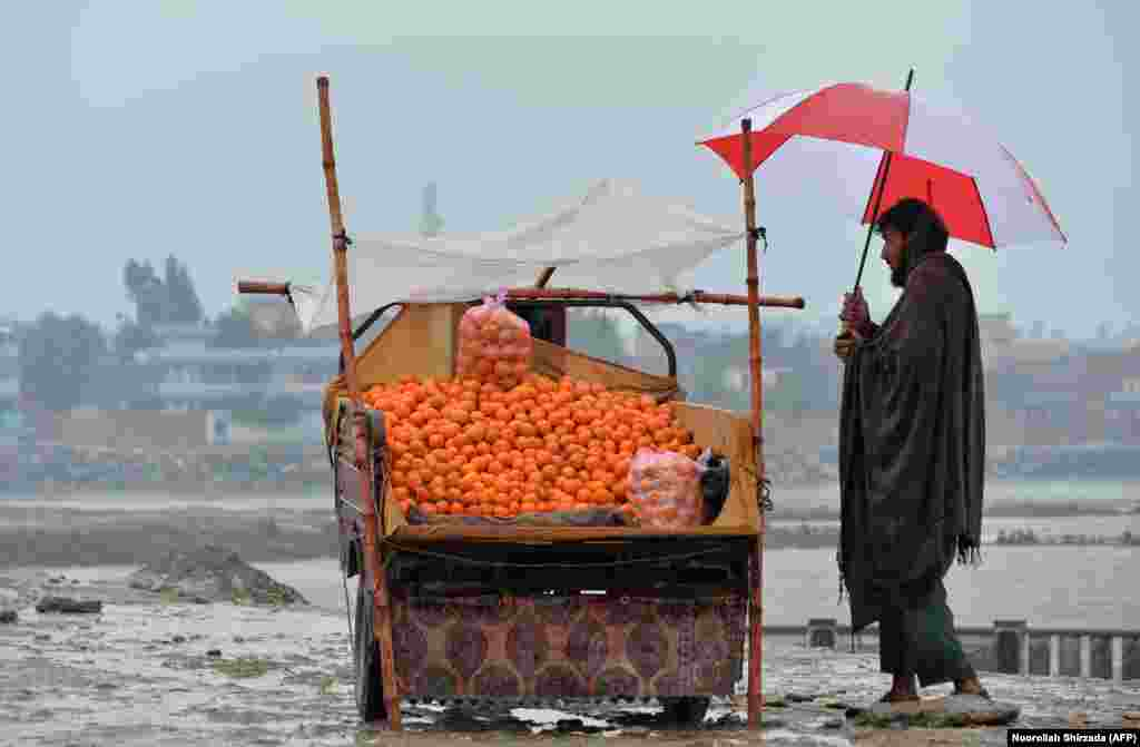 An Afghan street vendor selling oranges waits for customers on a rainy day on the roadside in Jalalabad. (AFP/Noorullah Shirzada)