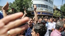 IRAN -- A group of protesters chant slogans at the main gate of old grand bazaar in Tehran, Iran, Monday, June 25, 2018. Protesters in the Iranian capital swarmed its historic Grand Bazaar on Monday, news agencies reported, and forced shopkeepers to close