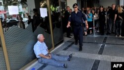 A man sits on the sidewalk crying outside a national bank branch as pensioners queue to withdraw their pensions, with a limit of 120 euros, in Thessaloniki.