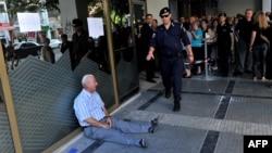 Фото 3 липня 2015 року: під банком у місті Тессалоніки плаче пенсіонер Йоргос Хацифотіадіс, який відстояв понад три години, щоб узяти 120 євро пенсії за дружину, та йому не дали
