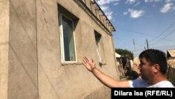 Мурат Абдижаппаров показывает трещины на стене своего дома.